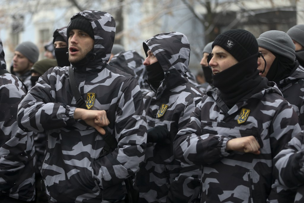 Volunteers with the right-wing paramilitary Azov National Corps salute during a rally on the snowy streets in front of the Ukrainian parliament in Kie