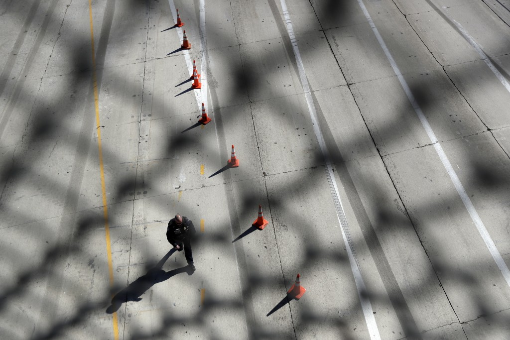 An official walks along the empty lanes of Interstate 5, where it reaches the San Ysidro port of entry, after closing the port Sunday, Nov. 25, 2018, ...