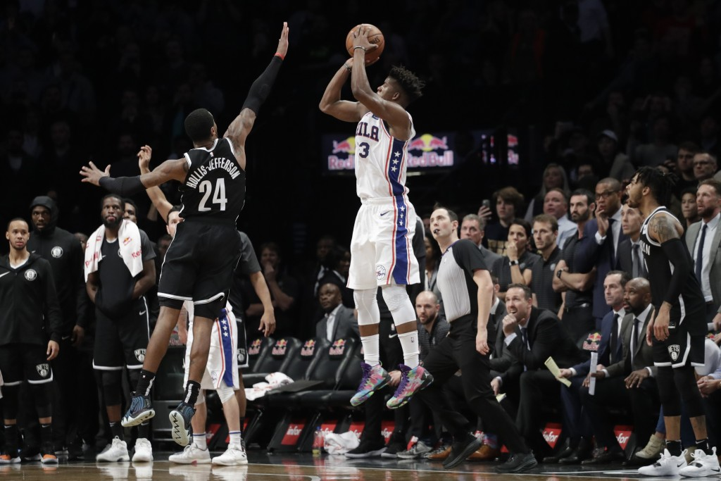 Philadelphia 76ers' Jimmy Butler (23) hits a game-winning three-point shot over Brooklyn Nets' Rondae Hollis-Jefferson (24) in the fourth quarter of a