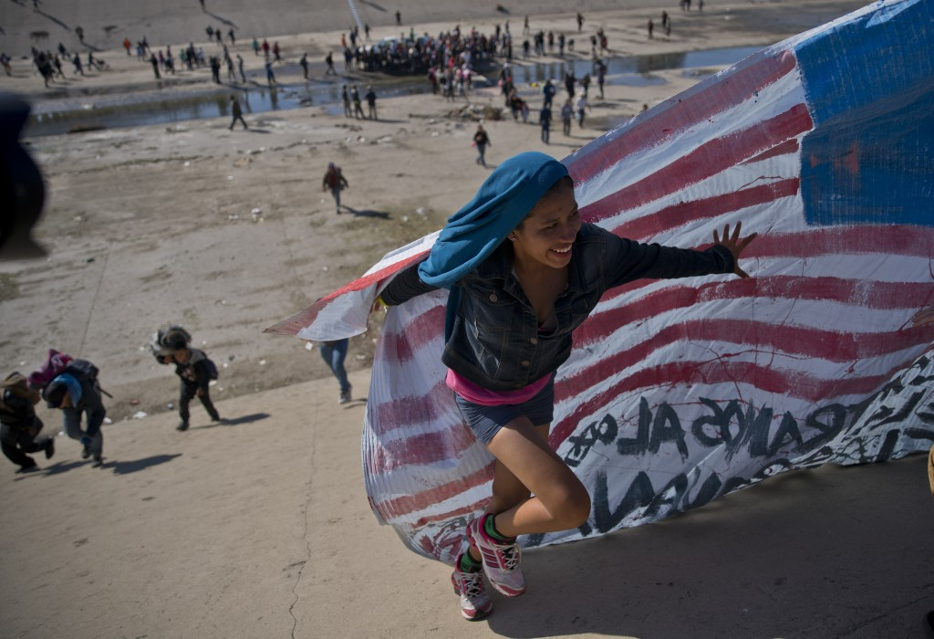 A migrant woman helps carry a handmade U.S. flag up the riverbank at the Mexico-U.S. border after getting past Mexican police at the Chaparral border