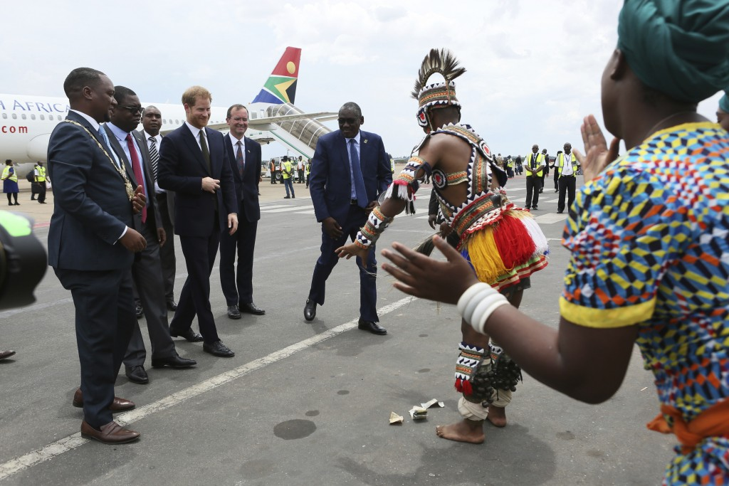 Zambian traditional dancers perform for Britain's Prince Harry, centre left, upon his arrival at Kenneth Kaunda airport in Lusaka, Monday, Nov. 26, 20