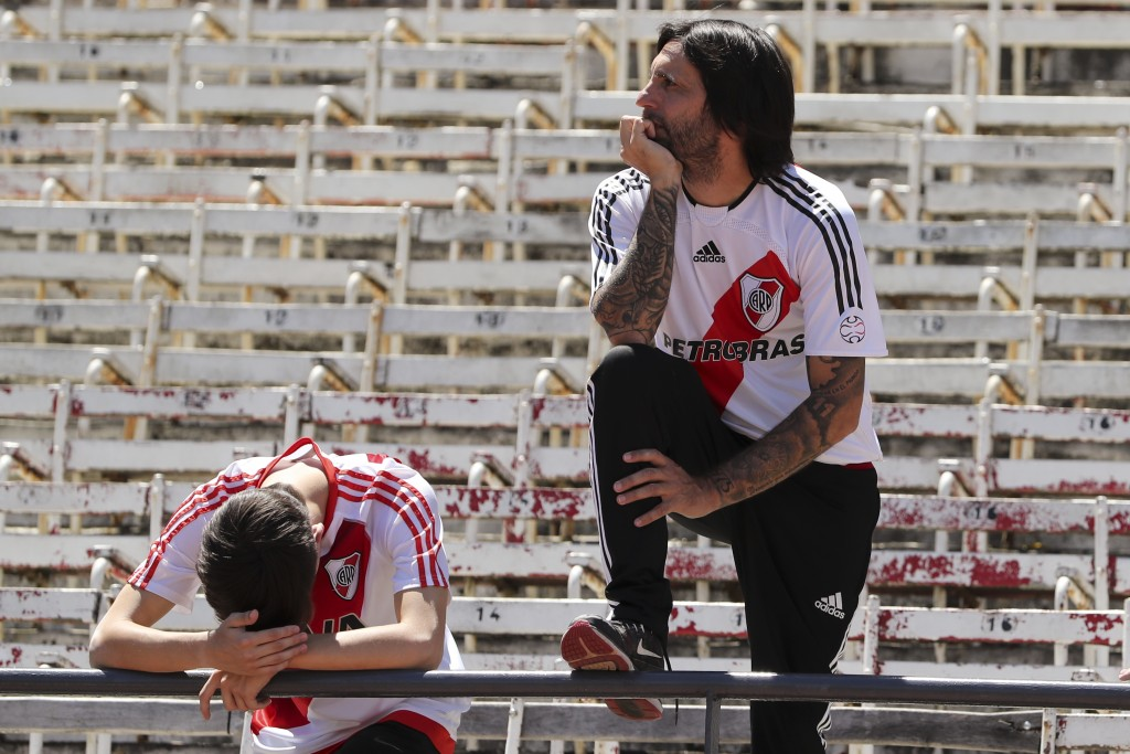 Fans of Argentina's River Plate react to the announcement that the final Copa Libertadores soccer match against Argentina's Boca Juniors was suspended...