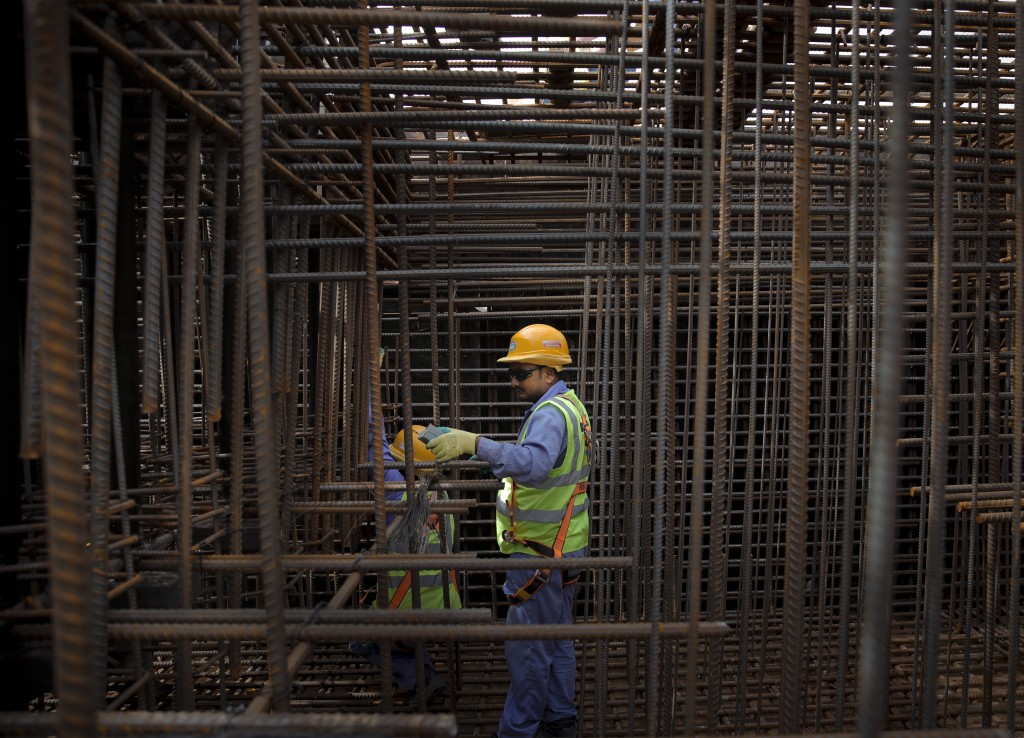 In this Wednesday, Oct. 31, 2018 picture, men install foundation steel reinforcement bars on the construction site of the Ras Abu Aboud stadium in Doh