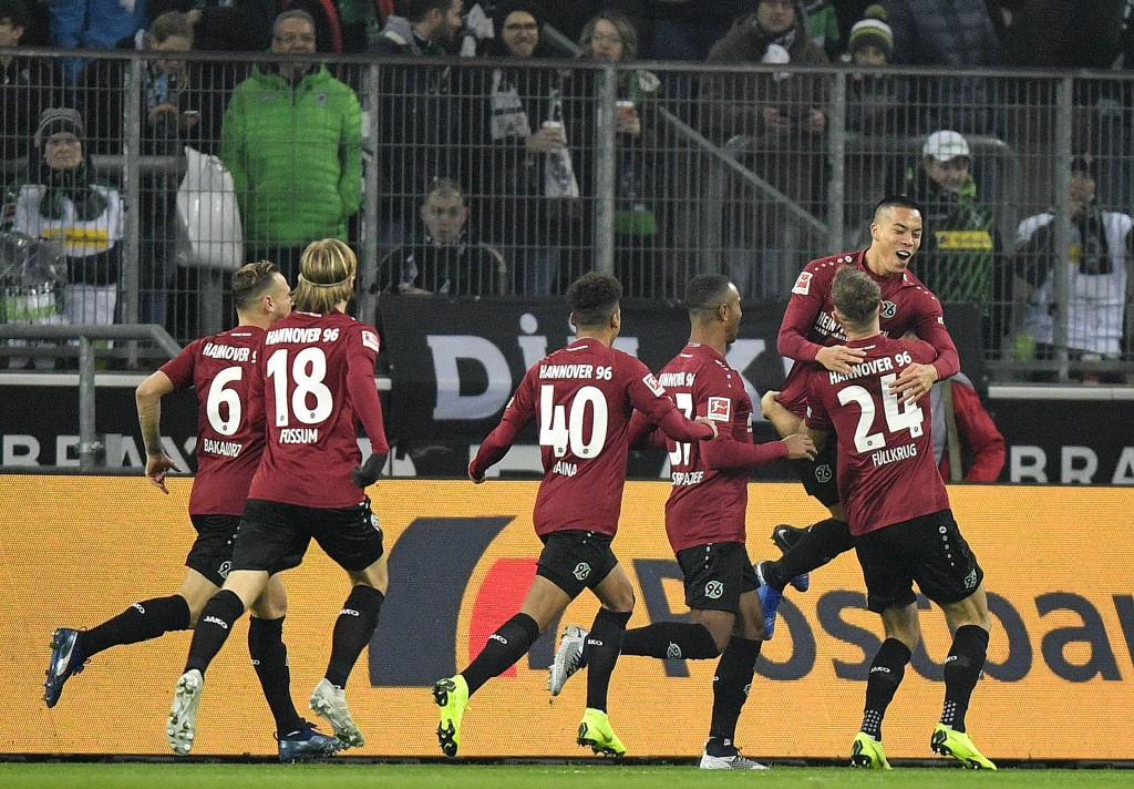 Hannover's Bobby Wood, right up, celebrates after scoring the opening goal in the first minute during the German Bundesliga soccer match between Borus...