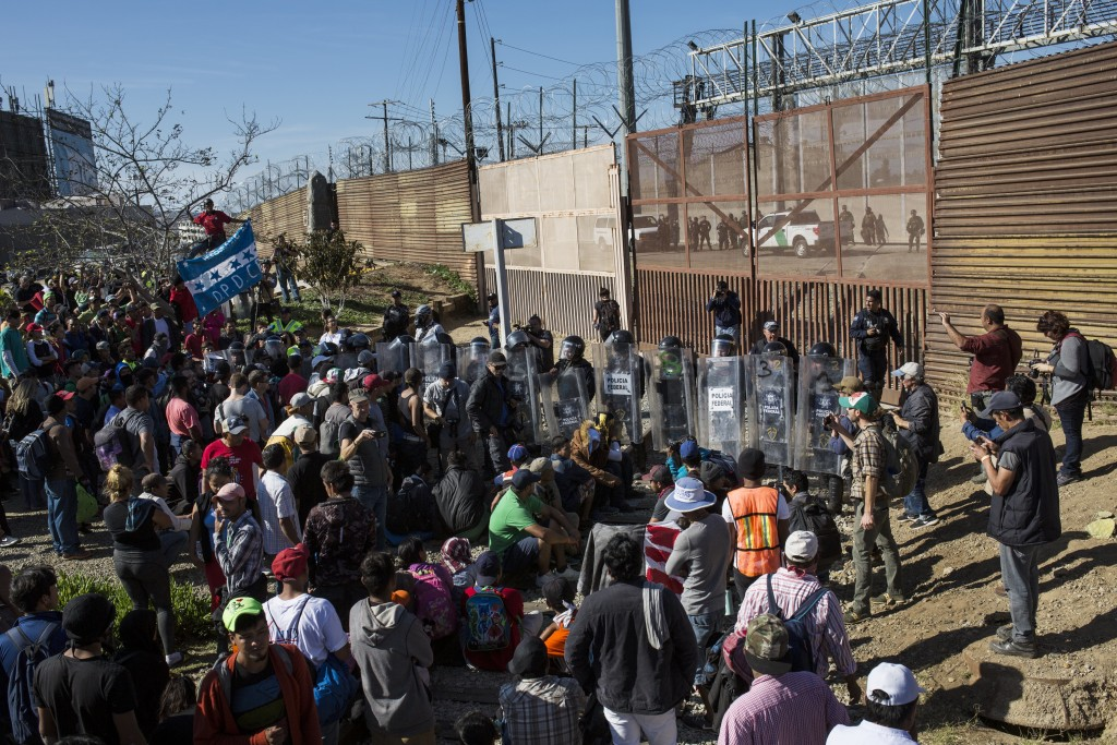 Migrants stand at the Mexico-U.S. border wall where Mexican federal police stand guard at the Chaparral crossing in Tijuana, Mexico, Sunday, Nov. 25, ...