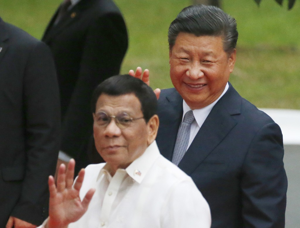 FILE - In this Tuesday, Nov. 20, 2018, file photo, Chinese President Xi Jinping, right, and Philippine President Rodrigo Duterte wave to the media fol