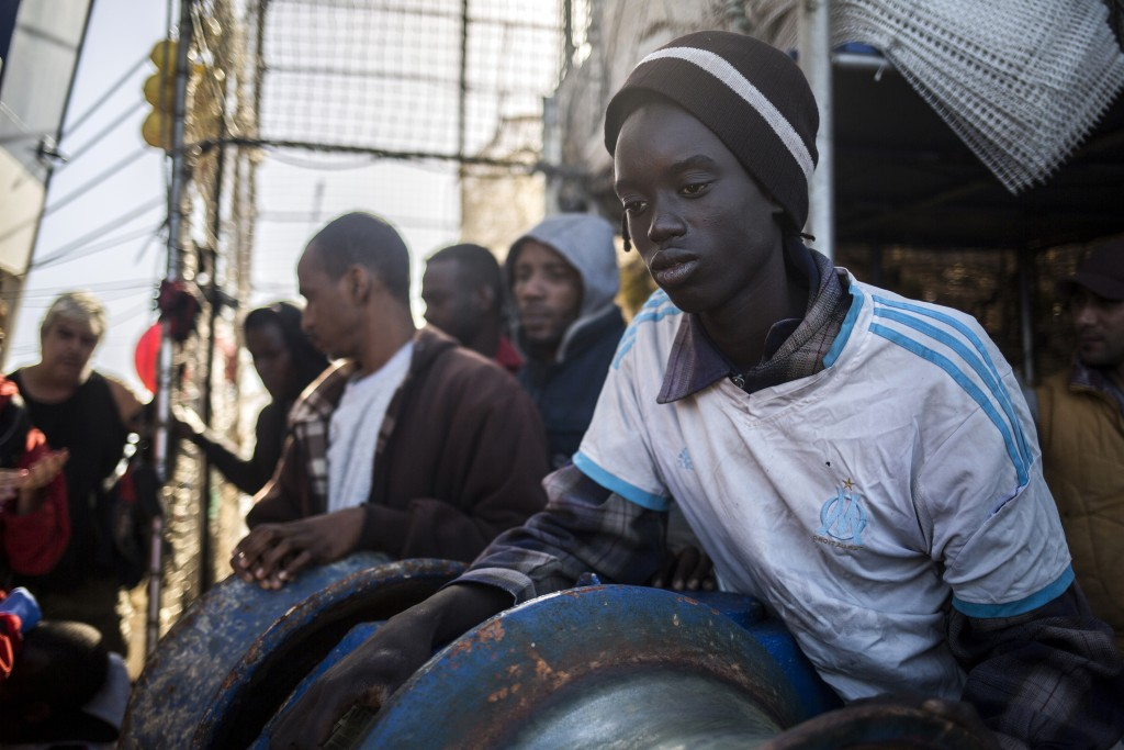 In this photo taken on Saturday, Nov. 24, 2018 photo, Migrants rest aboard Nuestra Madre de Loreto, a Spanish fishing vessel that rescued twelve migra
