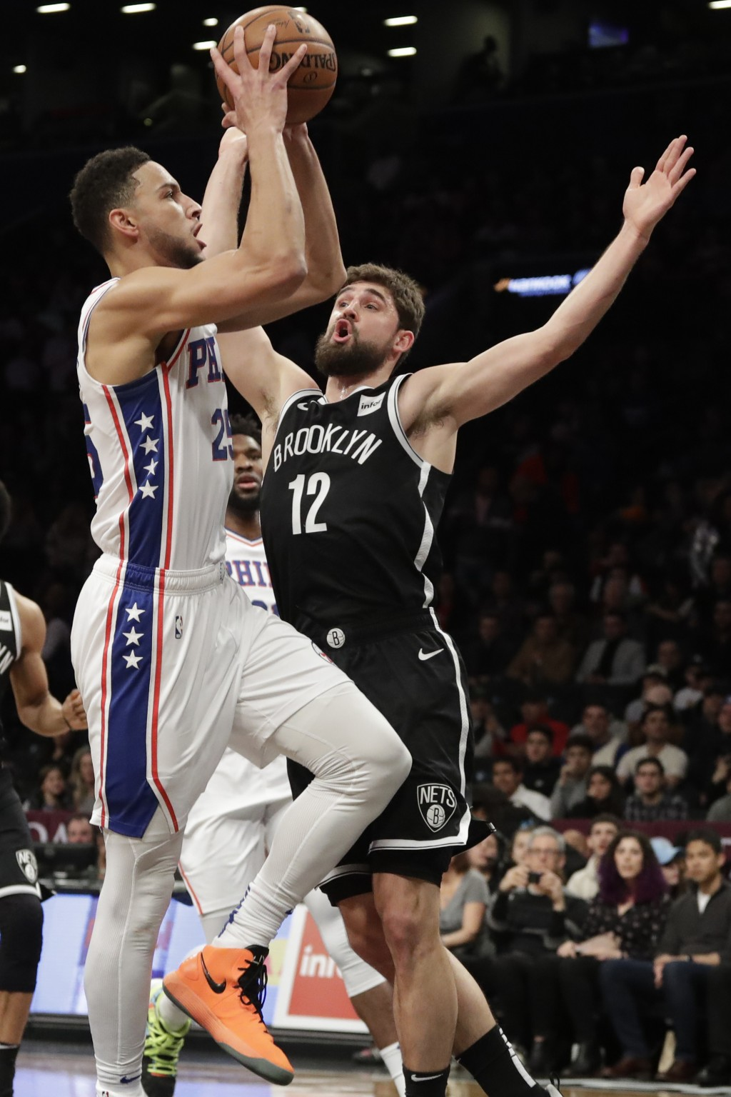 Philadelphia 76ers Ben Simmons (25) drives to the basket against Brooklyn Nets Joe Harris (12) in the first quarter of a basketball game, Sunday, Nov....