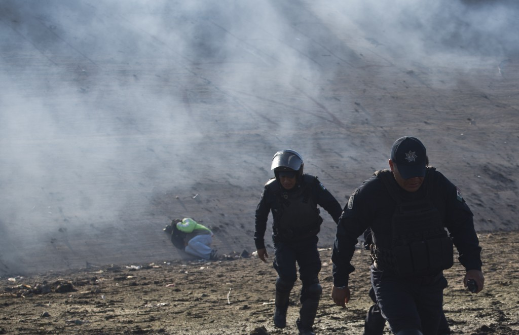 A Honduran migrant lies on the riverbank as Mexican police move away from tear gas fired by U.S. agents at the Mexico-U.S. border in Tijuana, Mexico,