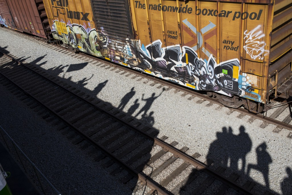 Shadows of migrants are cast on the railroad tracks at the Mexico-U.S. border in Tijuana, Mexico, Sunday, Nov. 25, 2018, as a group of migrants tries ...