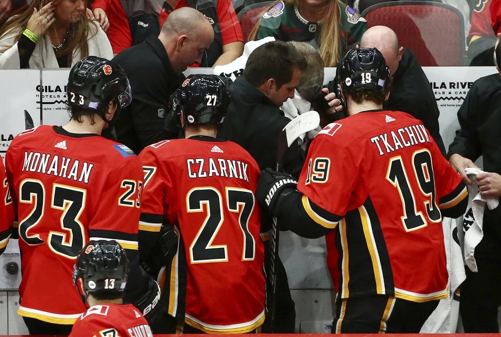 Calgary Flames center Sean Monahan (23), center Austin Czarnik (27) and left wing Matthew Tkachuk (19) look on as training staff treat head coach Bill