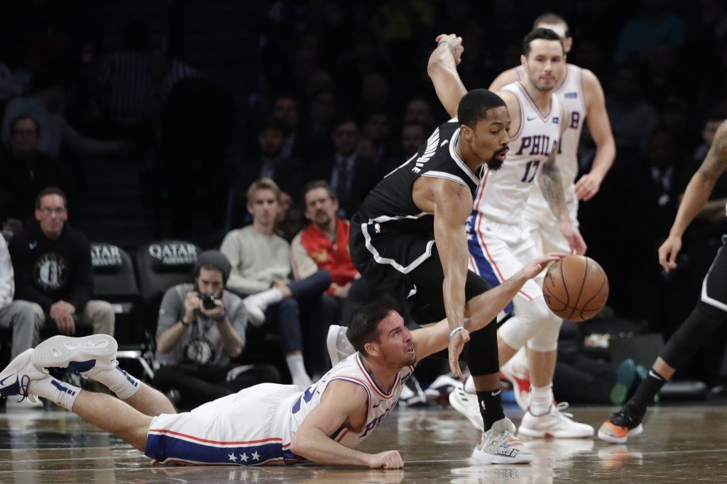 Philadelphia 76ers' T.J. McConnell falls to the floor attempting to steal a rebound from Brooklyn Nets' Zhaire Smith in the first quarter of an NBA ba...