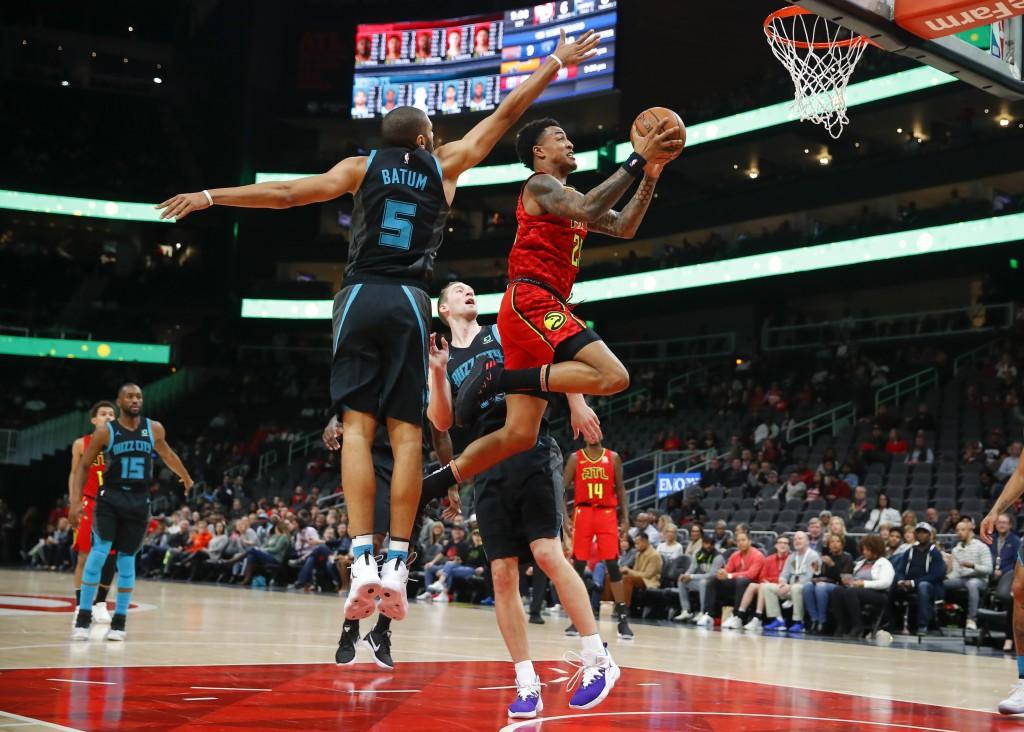 Atlanta Hawks forward John Collins (20) goes up to shoot as Charlotte Hornets forward Nicolas Batum (5) defends in the first half of an NBA basketball