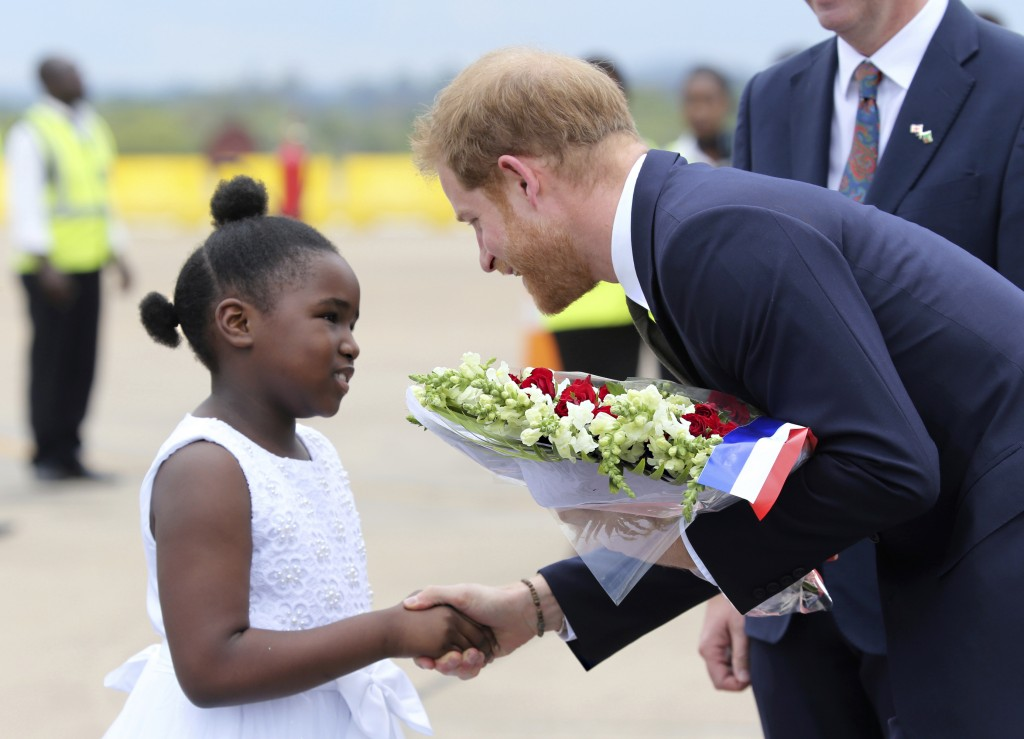 Britain's Prince Harry receives flowers from a girl upon his arrival at Kenneth Kaunda airport in Lusaka, Monday, Nov. 26, 2018. Prince Harry is on a