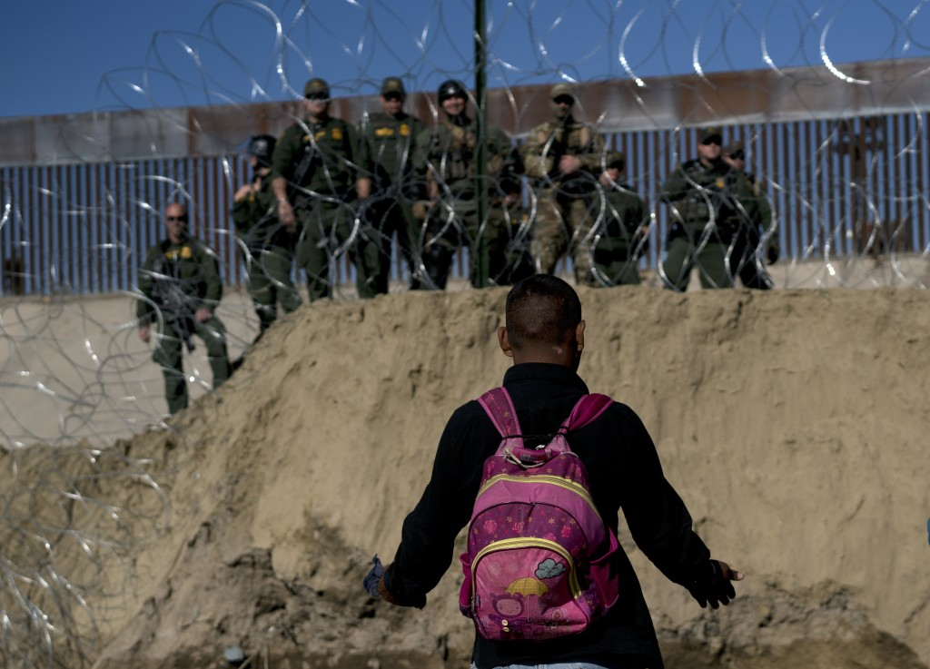 A Honduran migrant converses with U.S border agents on the other side of razor wire after they fired tear gas at migrants pressuring to cross into the