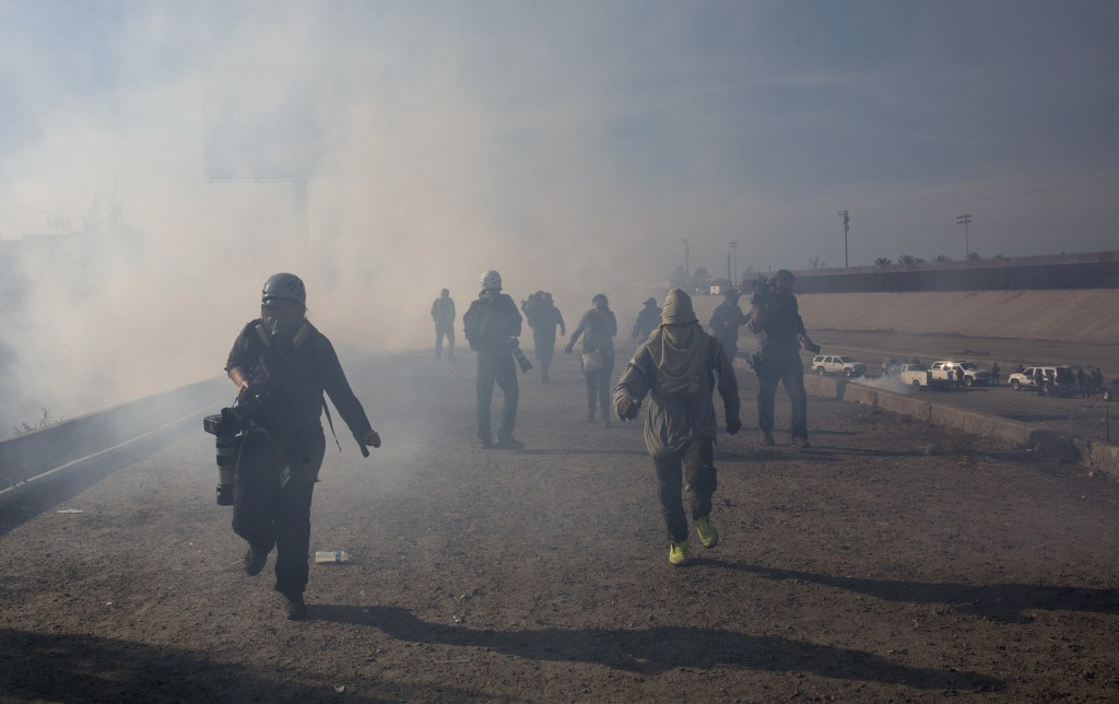 Migrants run from tear gas launched by U.S. agents, amid photojournalists covering the Mexico-U.S. border, after a group of migrants got past Mexican
