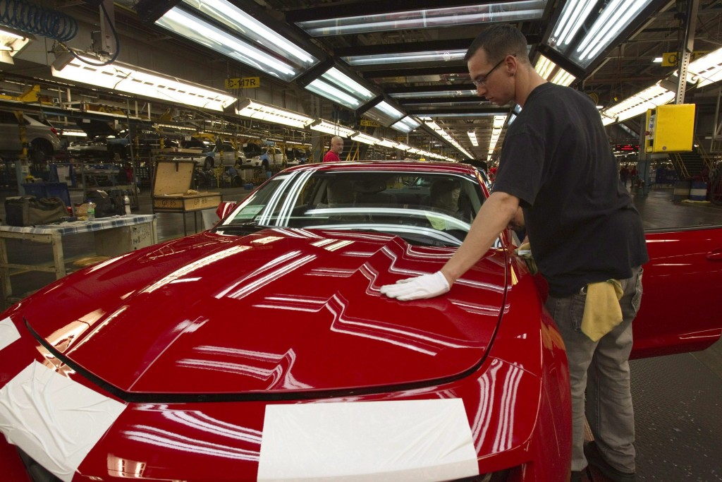FILE - In this June 10, 2011, file photo, a worker checks the paint on a Camaro at the GM factory in Oshawa, Ontario. General Motors is closing a Cana...