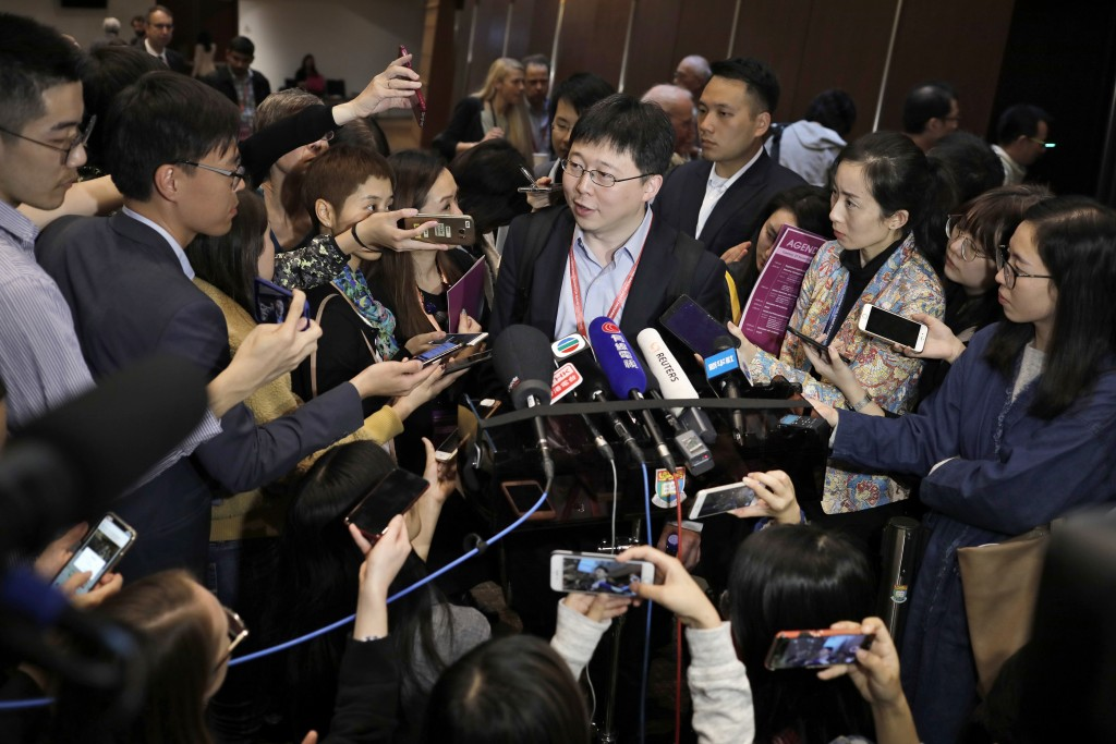 Feng Zhang, center, an institute member of Harvard and MIT's Broad Institute, is surrounded by reporters while speaking on the issue of world's first