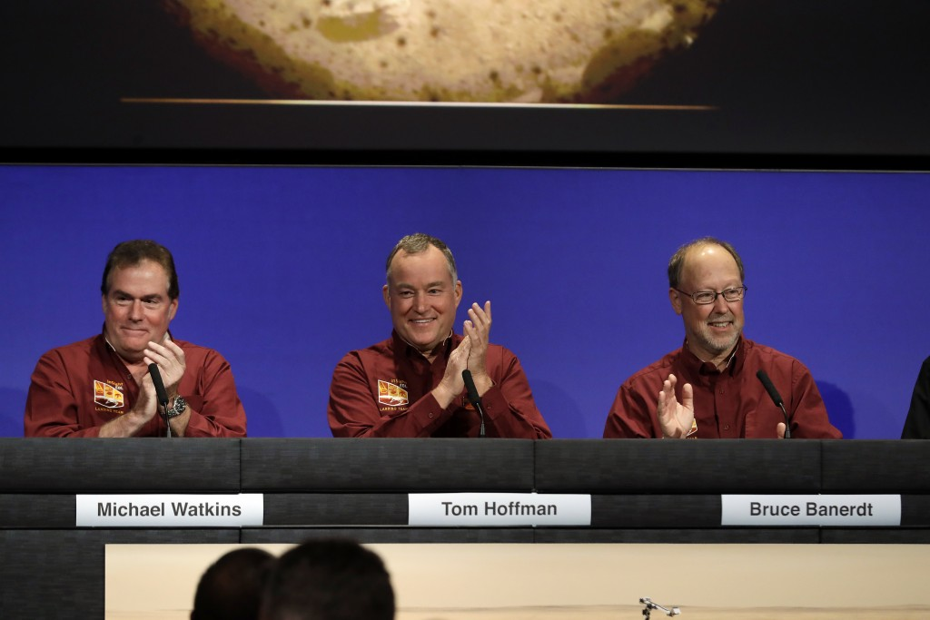 NASA officials, from left, Michael Watkins, Tom Hoffman, and Bruce Banerdt celebrate after the Mars landing of InSight at NASA's Jet Propulsion Labora