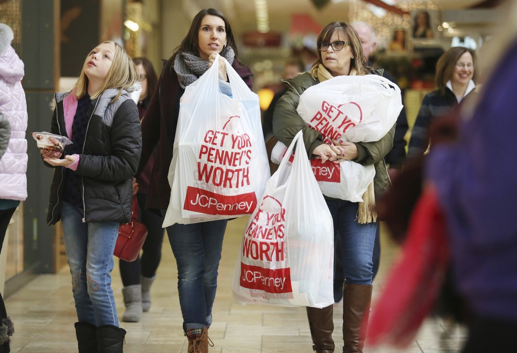 FILE- In this Nov. 23, 2018, file photo Shauna Turlipof, left, and Kathi Bankes make their way through other Black Friday shoppers at the Viewmont Mal