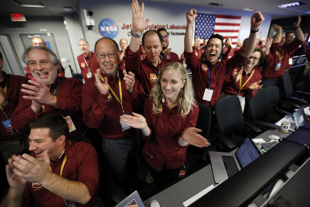 Engineers celebrate as the InSight lander touch downs on Mars in the mission support area of the space flight operation facility at NASA's Jet Propuls