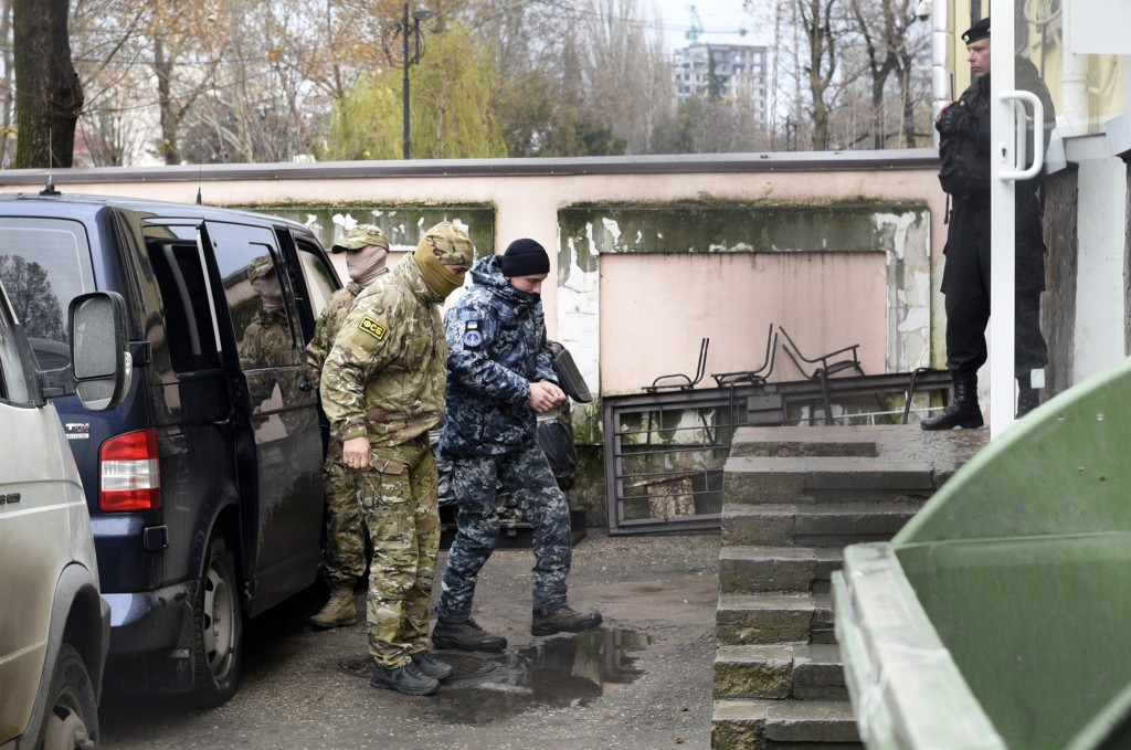 A Ukrainian sailor, center, is escorted by Russian intelligence agency FSB officer, left of him, to a court room in Simferopol, Crimea, Tuesday, Nov. ...