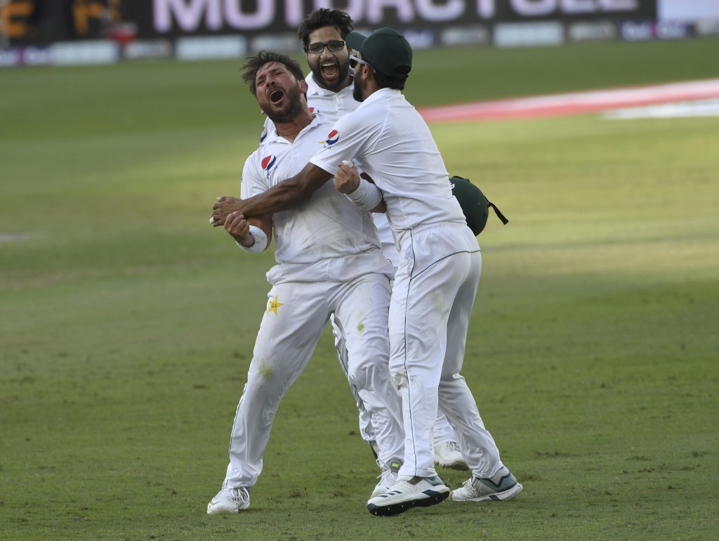 Pakistan's bowler Yasir Shah (L) reacts with Imam-ul-Haq (C) and Hasan Ali victory in a cricket test match against New Zealand in Dubai, United Arab E