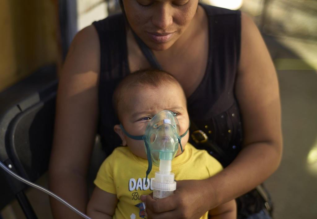 Honduran migrant Janet Zuniga holds her five-month-old son Linder, as he receives medical treatment outside a shelter, Monday, Nov. 26, 2018, in Tijua...