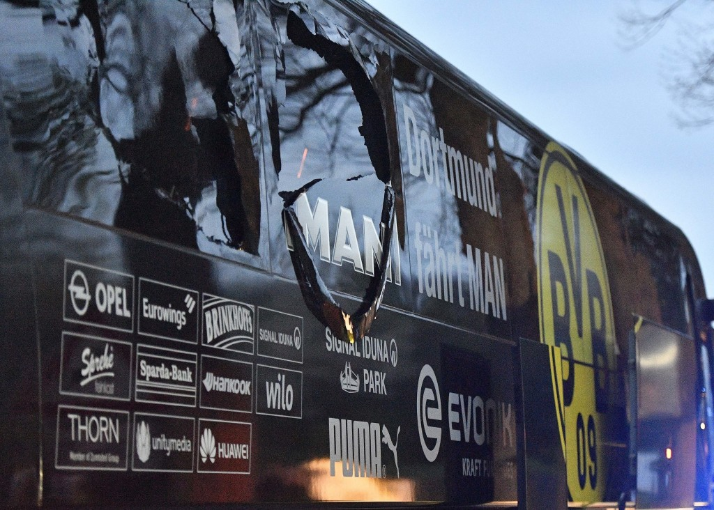 FILE - In this April 11, 2017 file photo a window of Dortmund's team bus is damaged after an explosion before the Champions League quarterfinal soccer