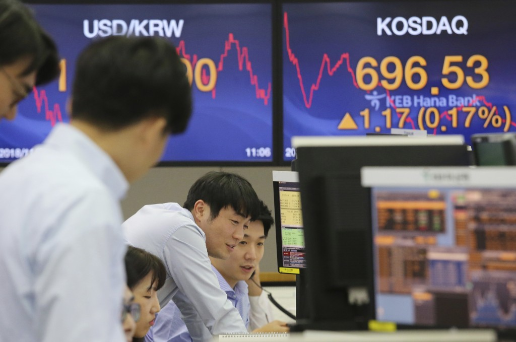 Currency traders watch monitors at the foreign exchange dealing room of the KEB Hana Bank headquarters in Seoul, South Korea, Tuesday, Nov. 27, 2018. ...