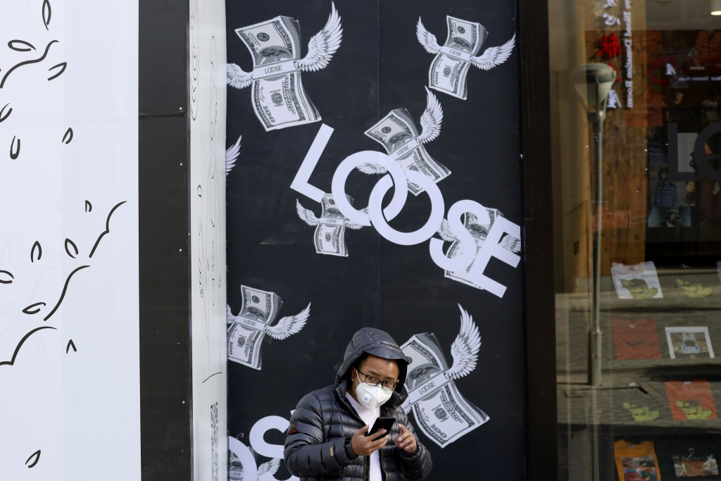 A man stands near a billboard depicting bundles of flying U.S. dollars at a retail district in Beijing, China, Tuesday, Nov. 27, 2018. Asian markets c...