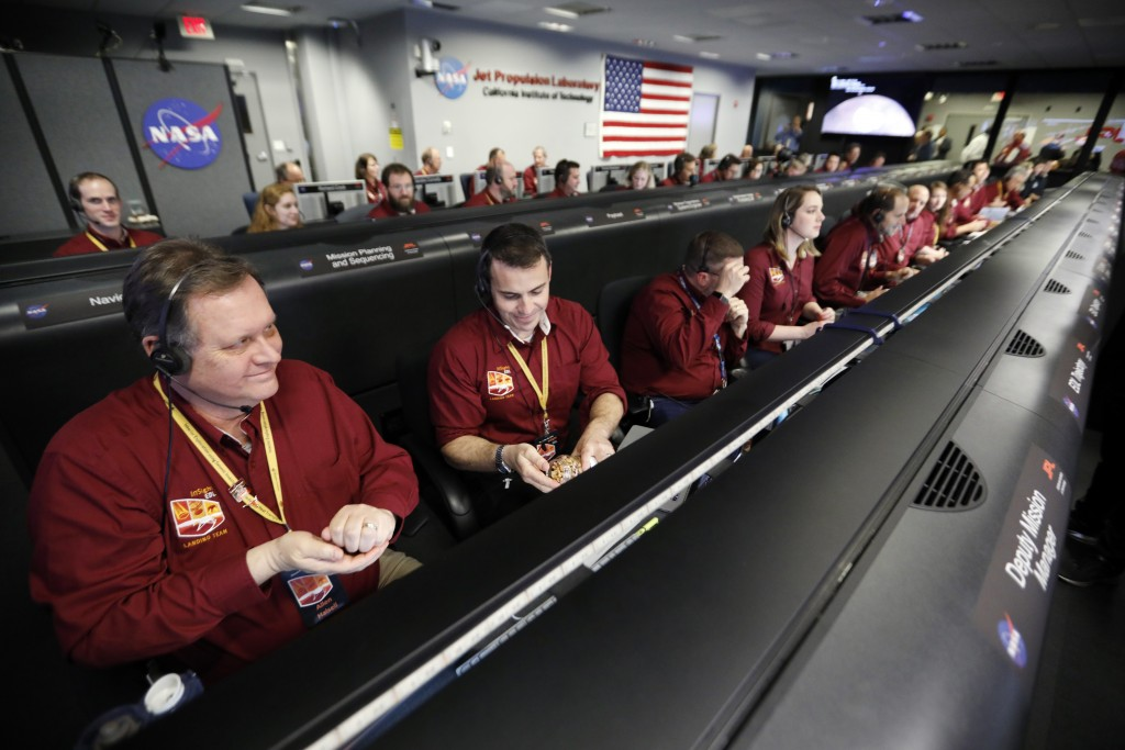 Engineers monitor the landing of InSight in the mission support area of the space flight operation facility at NASA's Jet Propulsion Laboratory Monday...