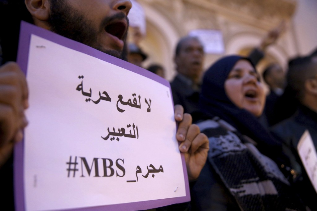 """An activist holds up a placard that reads """"No to repression of freedom of expression #MBS assassin"""" on the eve of Saudi Crown Prince Mohammed bin Salm"""