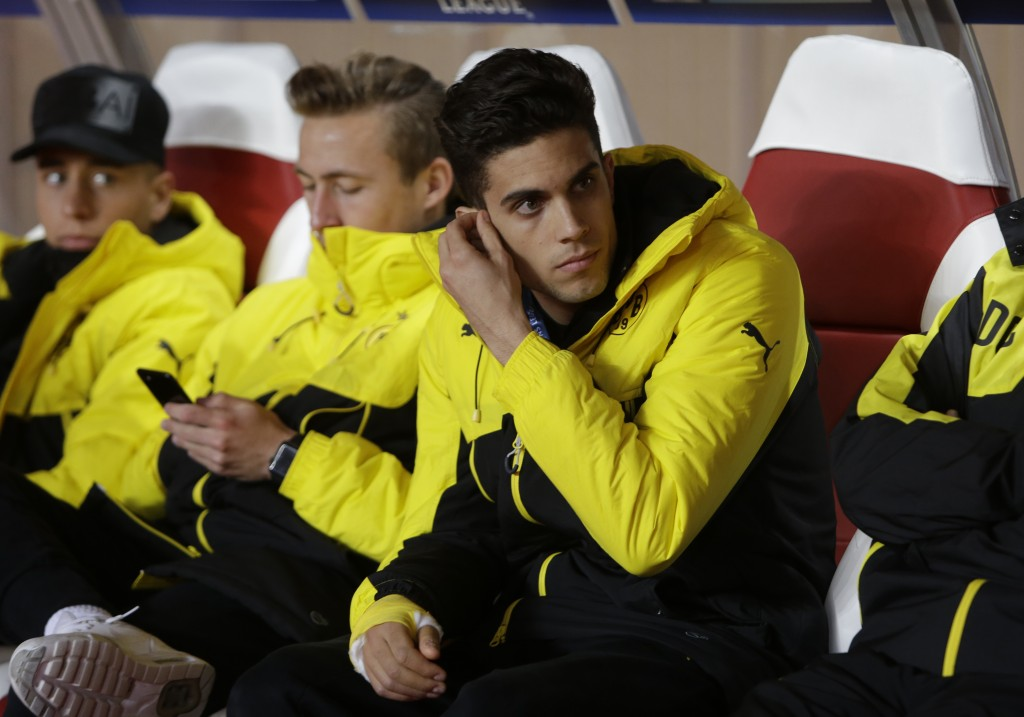 FILE - In this April 19, 2017 file photo Dortmund's Marc Bartra wears a cast on his arms after he was injured in the explosion as he sits on the bench...