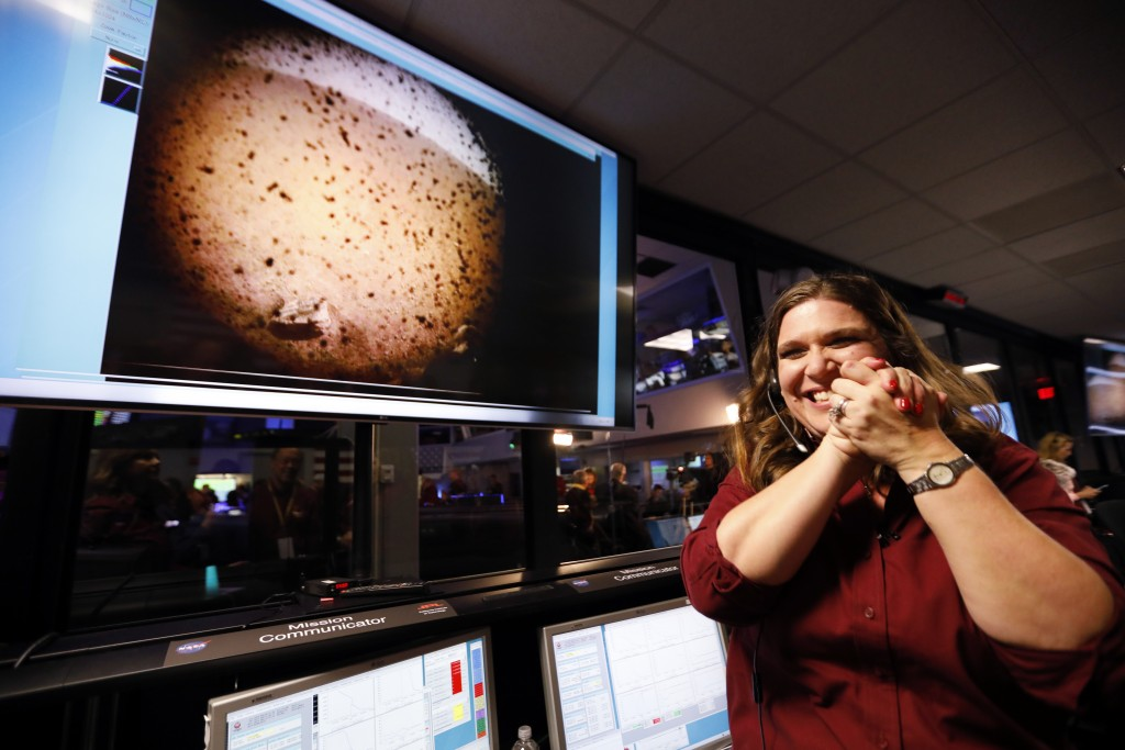 An engineer smiles next to an image of Mars sent from the InSight lander shortly after it landed on Mars in the mission support area of the space flig