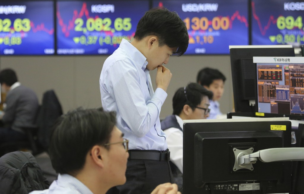 A currency trader watches monitors at the foreign exchange dealing room of the KEB Hana Bank headquarters in Seoul, South Korea, Tuesday, Nov. 27, 201