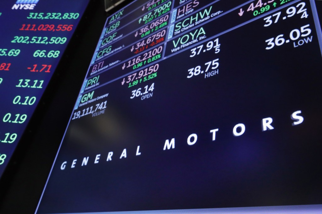 The logo for General Motors appears above a trading post on the floor of the New York Stock Exchange, Monday, Nov. 26, 2018. General Motors will lay o
