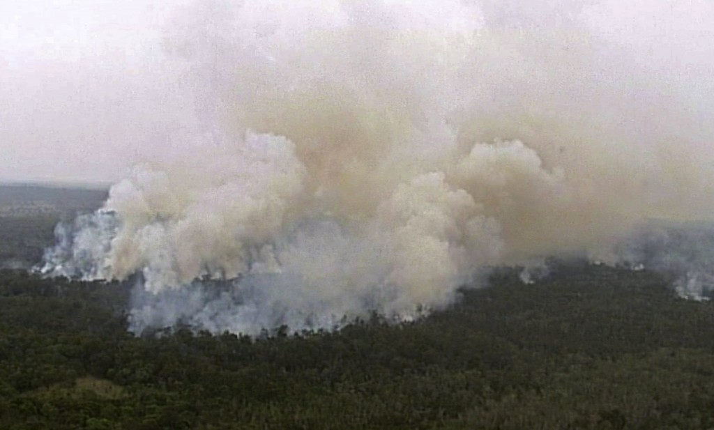 In this image made from aerial video taken Tuesday, Nov. 27, 2018, wildfires spread across the landscape in the Deepwater area of Queensland, Australi