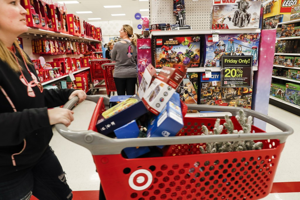 FILE- In this Friday, Nov. 23, 2018, file photo shoppers browse the aisles during a Black Friday sale at a Target store in Newport, Ky. Last year, 65