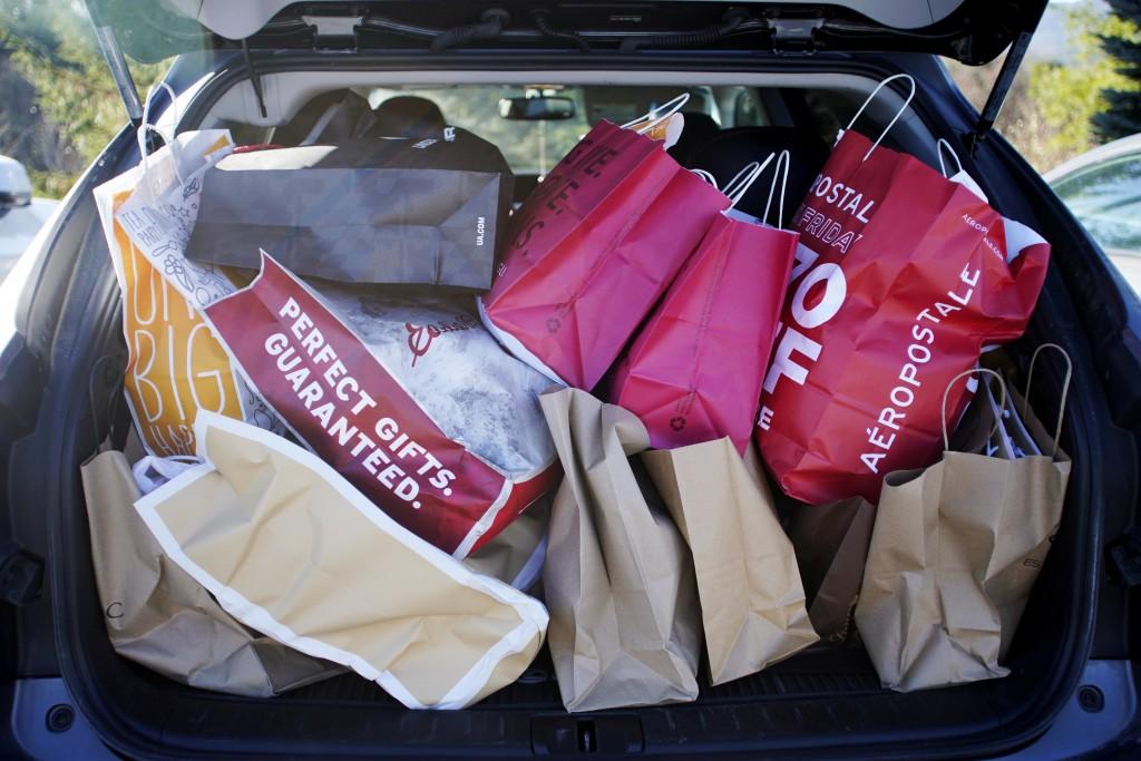 FILE- In this Nov. 23, 2018, file photo shopping bags are stuffed into a car at Prime outlets on Black Friday in Lee, Mass. Last year, 65 percent of m...