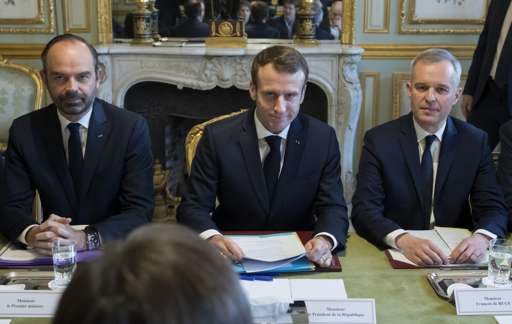 French President Emmanuel Macron, center, flanked by Prime Minister Edouard Philippe, left, and Ecology Minister Francois de Rugy, right, attends the