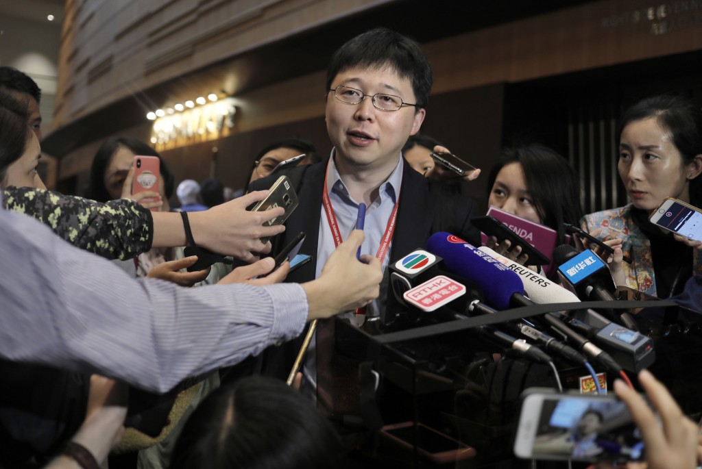 Feng Zhang, center, an institute member of Harvard and MIT's Broad Institute, reacts to reporters on the issue of world's first genetically edited bab...