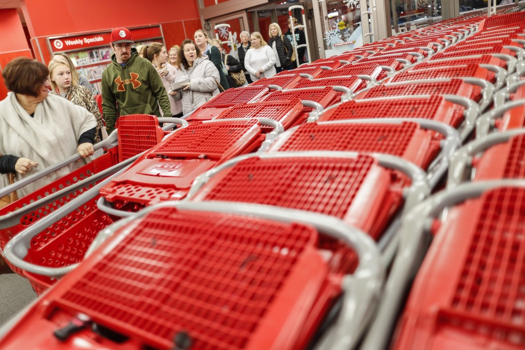 FILE- In this Friday, Nov. 23, 2018, file photo, shoppers enter and take their shopping carts during a Black Friday sale at a Target store in Newport,...