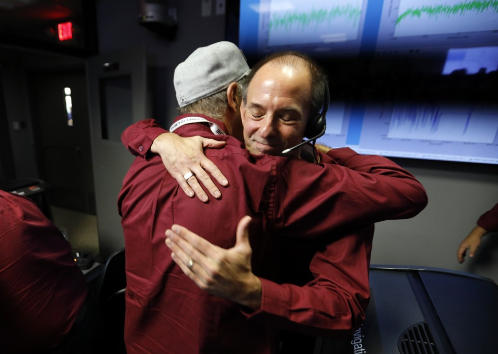 Engineers embrace after the Mars landing of InSight in the mission support area of the space flight operation facility at NASA's Jet Propulsion Labora