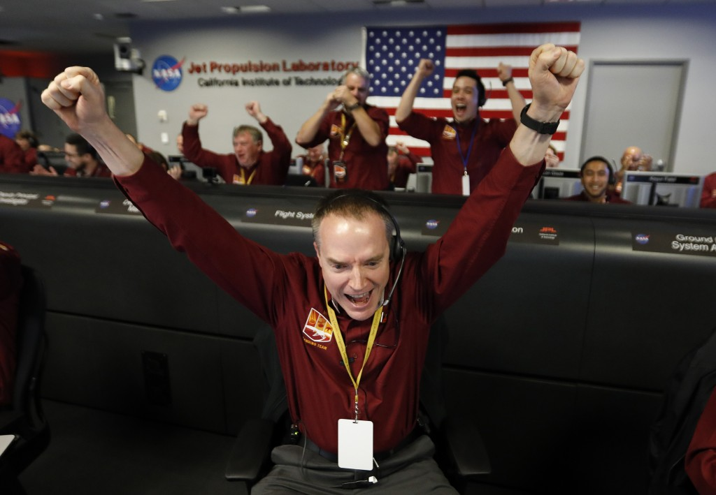 Engineer Kris Bruvold, bottom center, celebrates as the InSight lander touch downs on Mars in the mission support area of the space flight operation f...
