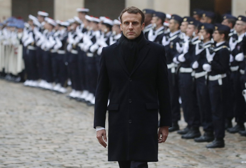 French President Emmanuel Macron inspects the honor guards during a military parade in the courtyard of the Invalides in Paris, France, Monday, Nov. 2...