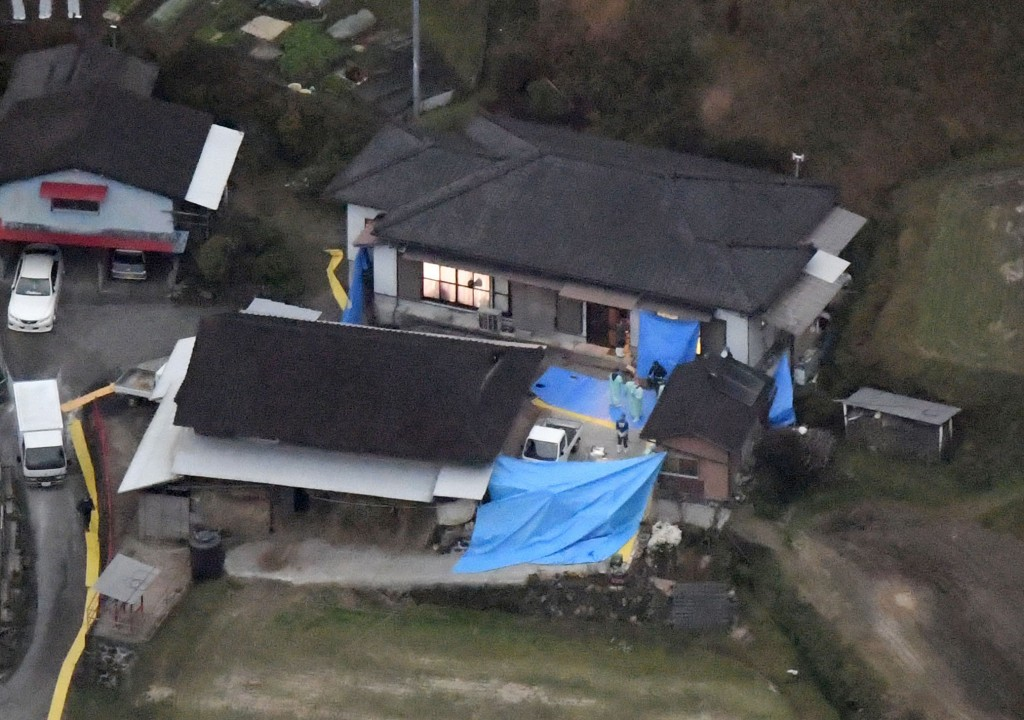 Blue plastic sheets cover the site where six bodies believed to be members of a family were found at a farmhouse in Takachiho, Miyazaki prefecture, so