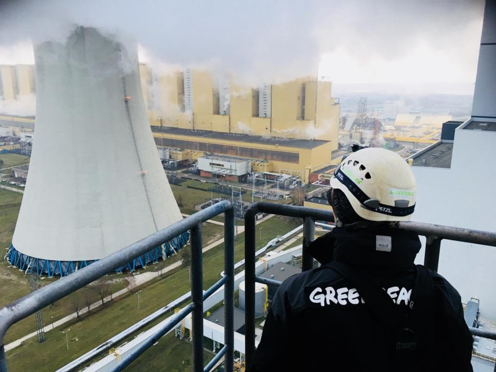 A Greenpeace activist looks at a chimney in the Belchatow power plant, the world's largest lignite-fired power station, in Belchatow, Poland, Tuesday,