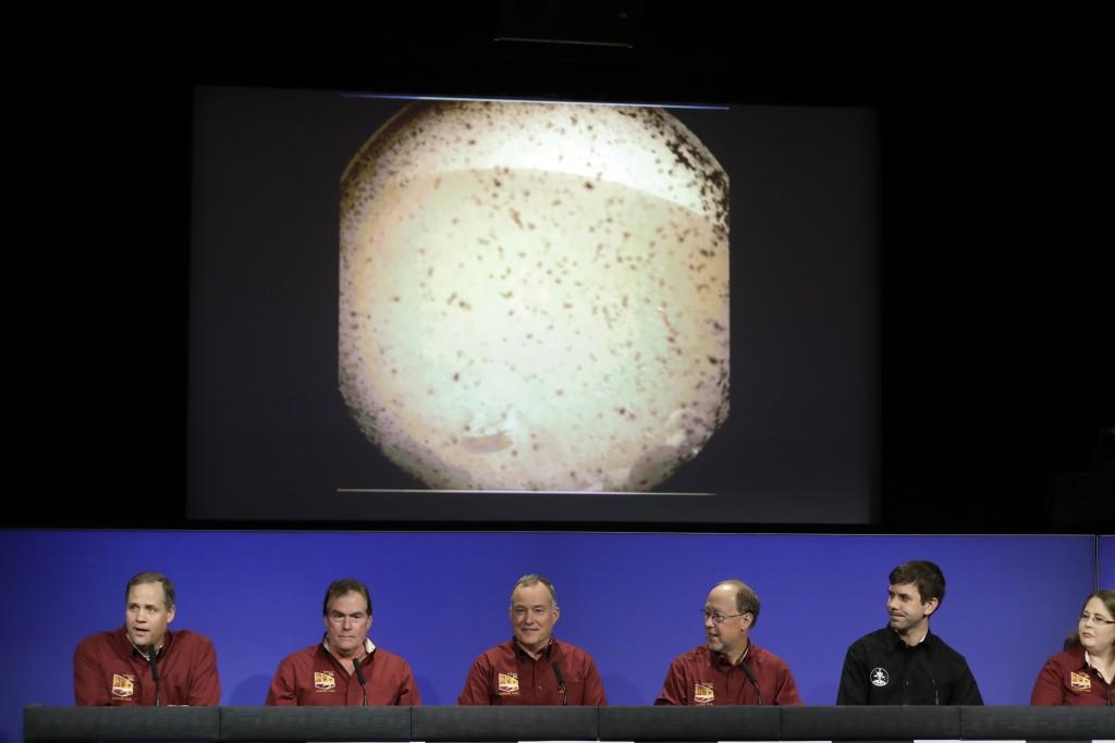 From left, NASA officials Jim Bridenstine, Michael Watkins, Tom Hoffman, Bruce Banerdt, Andrew Klesh and Elizabeth Barrett make statements under a pho