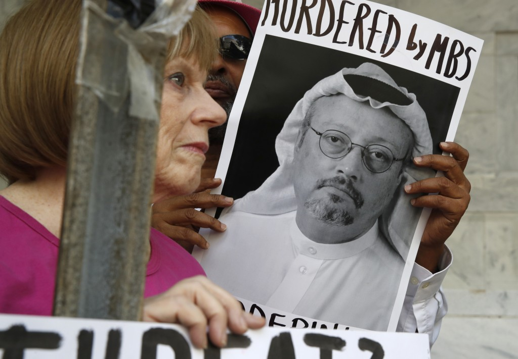 FILE - In this Oct. 10, 2018, file photo, people hold signs during a protest at the Embassy of Saudi Arabia about the disappearance of Saudi journalis...